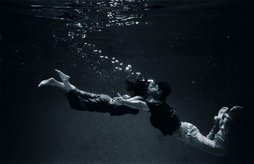 Underwater bride and groom kiss